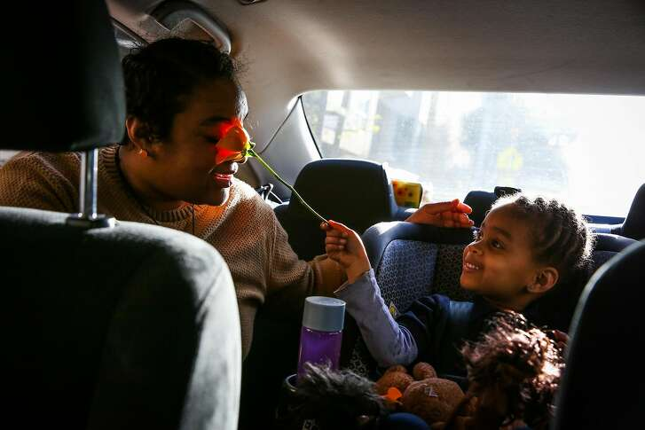 (l-r) Kailey Norris goofs around  with her daughter Khyla Robinson, 3, as she puts her in the car to go home from her pre-school in the Haight in in San Francisco, California, on Friday, April 14, 2017.