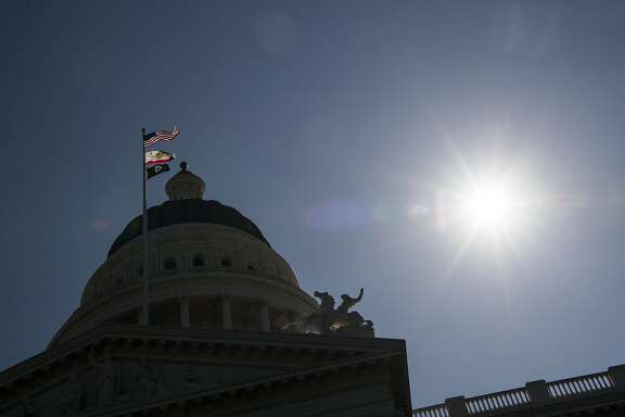 The American, California State, and POW/MIA flags fly in front of the California State Capitol building in Sacramento, California, U.S., on Thursday, March 30, 2017. California Governor Jerry Brown and legislative leaders proposed a plan to raise taxes and levy new fees to pay the bulk of $52.4 billion in transportation projects over 10 years. Photographer: David Paul Morris/Bloomberg