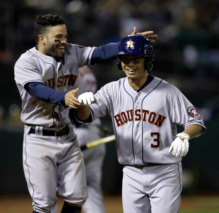 Jose Altuve couldn't be happier after new Astros teammate Nori Aoki, right, homered in the fifth inning Friday night against the Athletes. Photo: Ben Margot, STF / Copyright 2017 The Associated Press. All rights reserved.