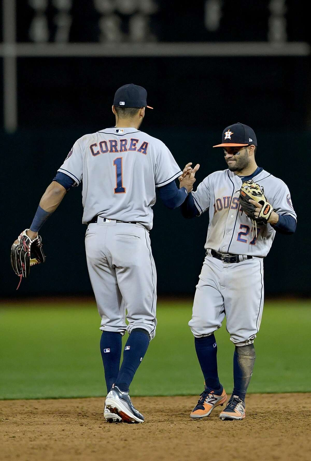 OAKLAND, CA - APRIL 14: Carlos Correa #1 and Jose Altuve #27 of the Houston Astros celebrates defeating the Oakland Athletics 7-2 at Oakland Alameda Coliseum on April 14, 2017 in Oakland, California. (Photo by Thearon W. Henderson/Getty Images)