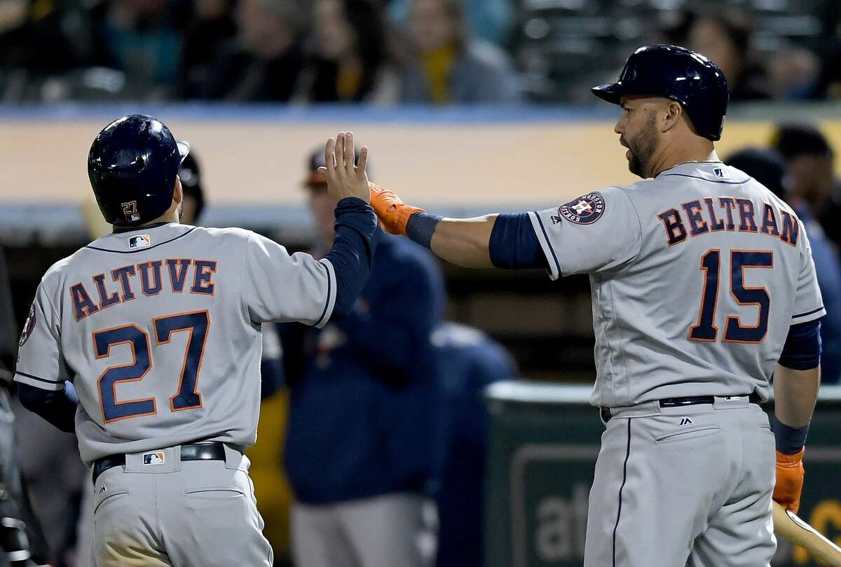 OAKLAND, CA - APRIL 14: Jose Altuve #27 of the Houston Astros is congratulated by Carlos Beltran #15 after Altuve scored on a throwing error by third baseman Trevor Plouffe #3 of the Oakland Athletics in the top of the seventh inning at Oakland Alameda Coliseum on April 14, 2017 in Oakland, California. (Photo by Thearon W. Henderson/Getty Images)