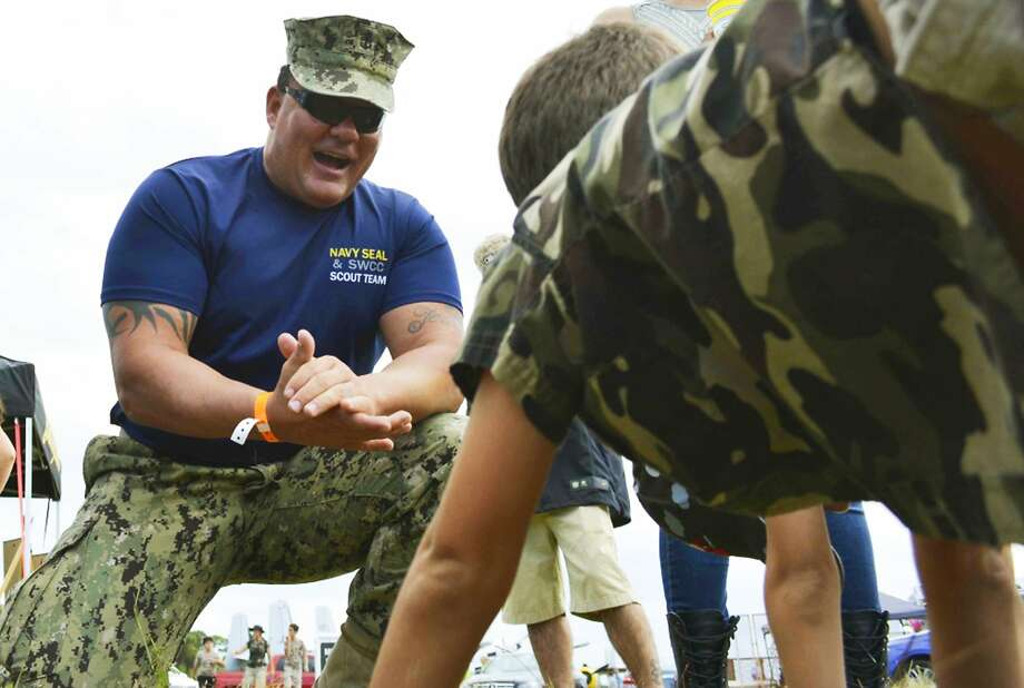 Navy SEAL Joseph Schmidt III encourages a youth to do pushups during a November air show in Stuart, Fla. Photo: Petty Officer 2nd Class Pyoung K. Yi, Associated Press