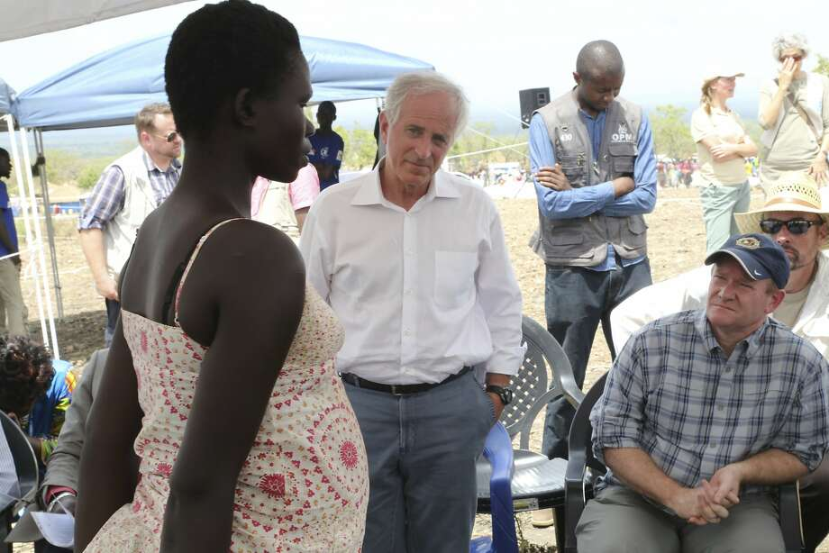 "In this photo taken on Friday, April 14, 2017, U.S Senators Bob Corker, center, and Chris Coons, right, speak with a South Sudanese refugee during a group discussion at the Bidi Bidi refugee settlement in northern Uganda. In a political climate dominated by President Donald Trump's slogan of ""America First,"" two U.S. senators are proposing making American food aid more efficient after meeting with victims of South Sudan's famine and civil war. After visiting the world's largest refugee settlement in northern Uganda, Democratic Sen. Chris Coons of Delaware told The Associated Press that the U.S. ""can deliver more food aid at less cost"" through foreign food aid reform. (AP/Photo/Justin Lynch) Photo: Justin Lynch, Associated Press"
