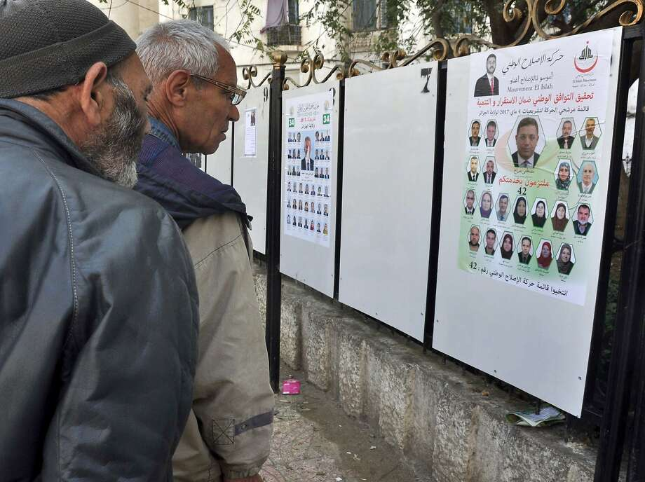 Residents of Algiers review posters this month for the May 4 legislative vote. Photo: Anis Belghoul, Associated Press