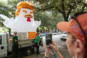 Jens and Melissa Moeller for a photo in front of an inflatable chicken shaped as President Donald Trump during a Tax March protest on Saturday, April 15, 2017, in Houston. (Brett Coomer / Houston Chronicle)