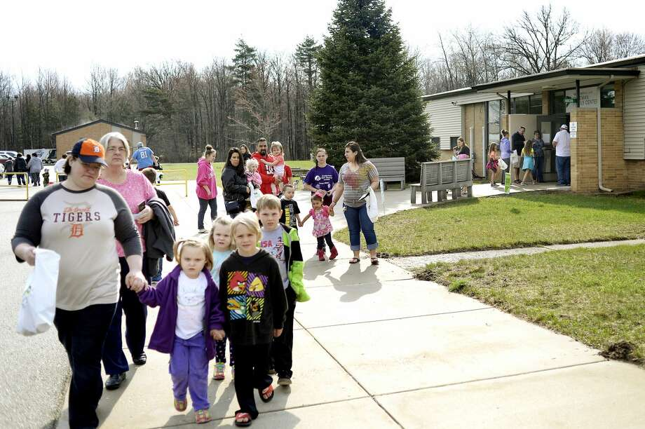 Participants leave the Greater Midland Coleman Family Center to start the egg hunt on Saturday in Coleman. Participants gathered clues that led them to stops at businesses, churches and the fire department around town where they collected eggs. After the hunt participants were welcomed back to the Coleman Family Center for food, games and prizes. Photo: NICK KING | Nking@mdn.net