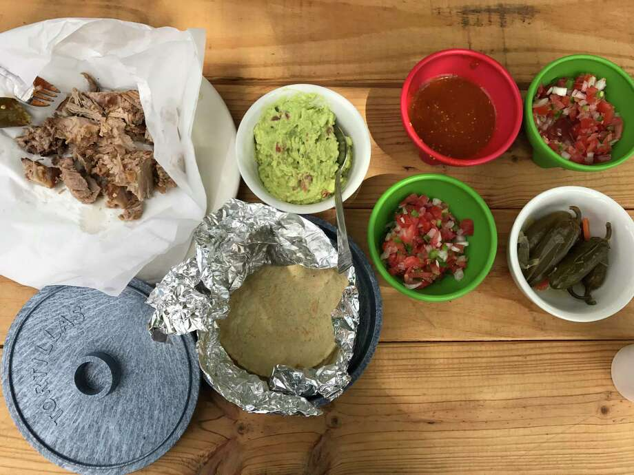 The carnitas goods at Carnitas Lonja on Roosevelt Avenue. A half-pound of carnitas with thick, gorgeous corn tortillas, basic but fresh and tasty guacamole and all the fixings. Photo: Emily Spicer /San Antonio Express-News / San Antonio Express-News