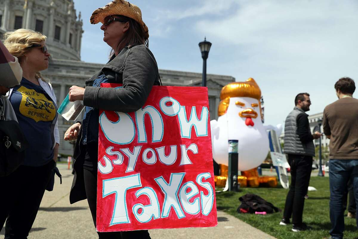 Lana Hurteau of Oakland holds a sign near an inflatable Trump chicken before Tax Day rally in San Francisco, Calif., on Saturday, April 15, 2017.