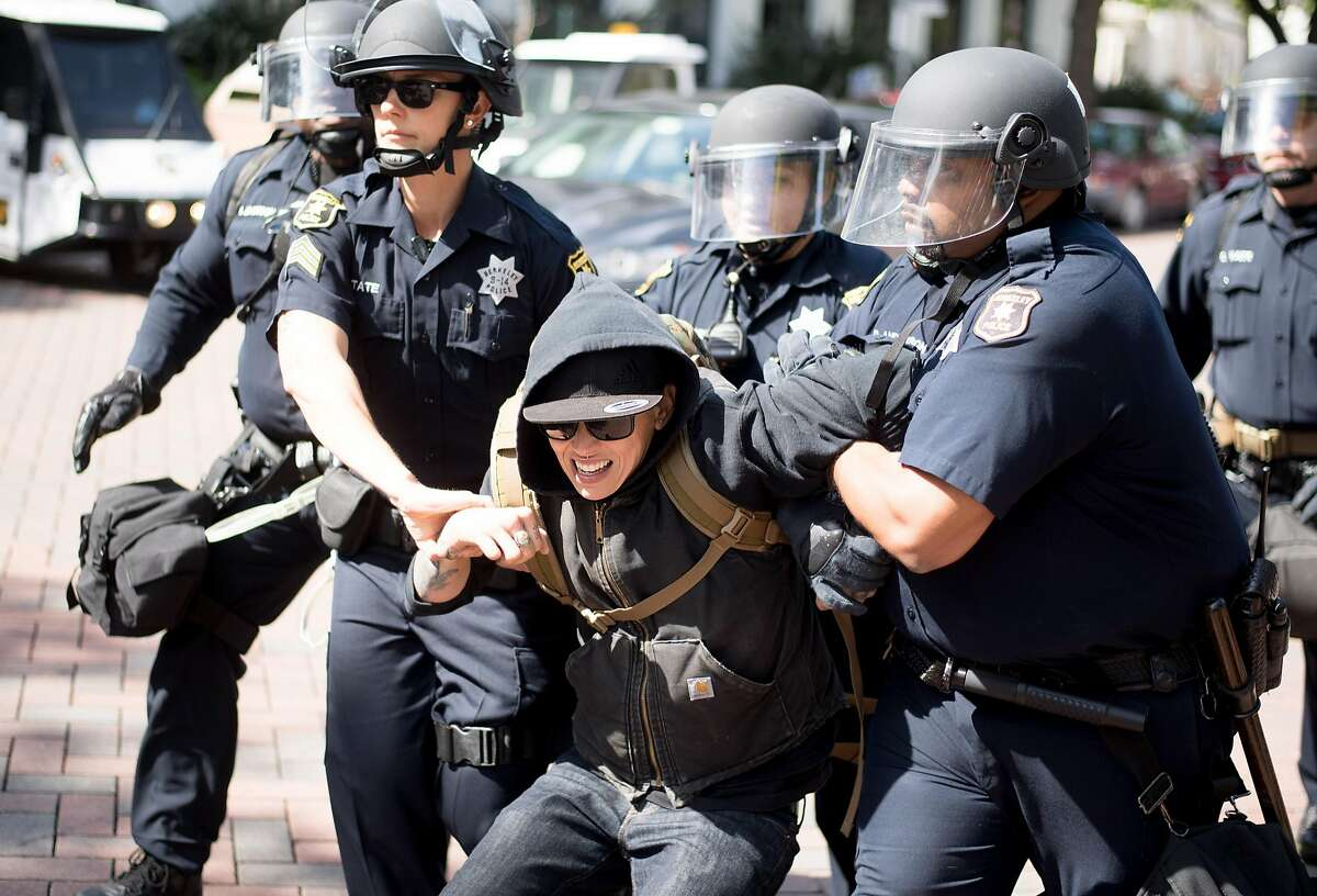 Police detain a protester against President Donald Trump on Saturday, April 15, 2017, in Berkeley, Calf.