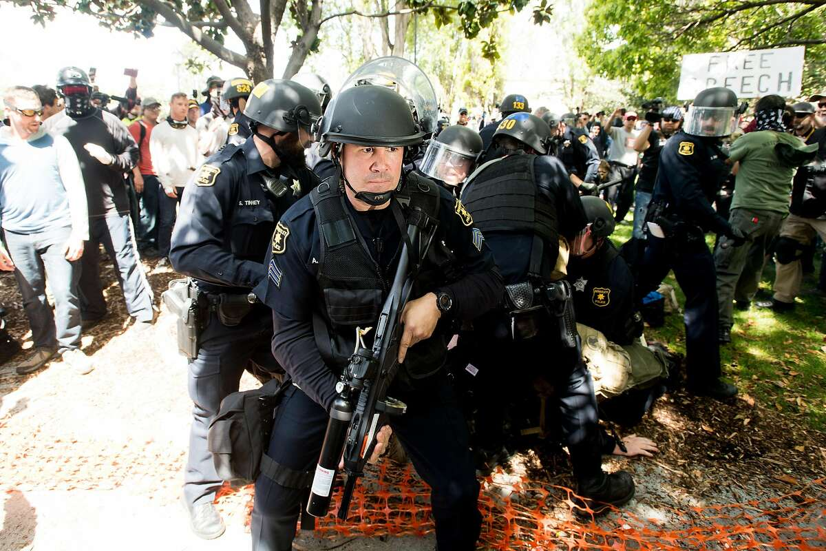 A police officer holds off demonstrators on Saturday, April 15, 2017, in Berkeley, Calf.