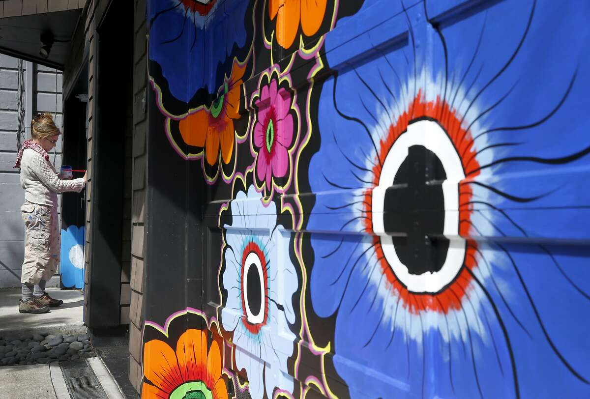 Muralist Megan Wilson paints a flower motif on a pair garage doors in the Haight Ashbury neighborhood of San Francisco, Calif. on Saturday, April 15, 2017. The Asian Art Museum commissioned Wilson to paint a series of floral murals throughout the city for its Flower Power exhibit to commemorate the 50th anniversary of the Summer of Love.