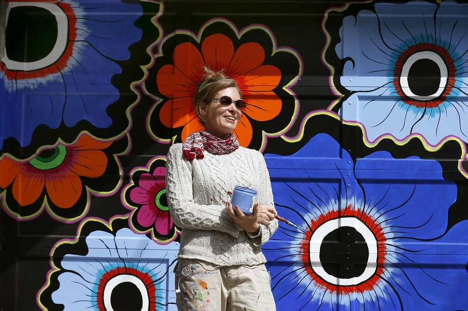 Muralist Megan Wilson paints a flower motif on a pair of garage doors in the Haight Ashbury neighborhood of San Francisco, Calif. on Saturday, April 15, 2017. The Asian Art Museum commissioned Wilson to paint a series of floral murals throughout the city for its Flower Power exhibit to commemorate the 50th anniversary of the Summer of Love. Photo: Paul Chinn, The Chronicle