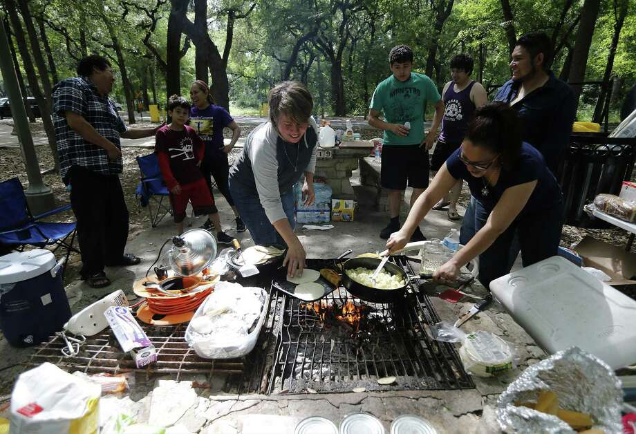 """Yadira Coronado (front right) and Juany Espino (center) help cook breakfast for their family while camping in Brackenridge Park on Saturday, Apr. 15, 2017. In annual fashion, campers stake a spot at Brackenridge to celebrate Easter weekend with family and friends. The city lifted the curfew on city parks on Thursday so people could claim their favorite camping spots. Seemingly quieter than usual some campers enjoyed the respite from city noise. """"It seems a little quieter this year, but it's not a bad thing,"""" said Jose Lazo. """"You get to feel more with nature."""" Many have made camping at Brackenridge an annual tradition while some are just starting like Gabriel Barrera who brought his wife and 15-month-old son to camp. """"I want to make it a family tradition,"""" Barrera said while trying to fly a kite with his son. Campers can stay overnight at 10 city parks until 11 p.m. Sunday. (Kin Man Hui/San Antonio Express-News) Photo: Kin Man Hui, Staff / San Antonio Express-News / ©2017 San Antonio Express-News"""
