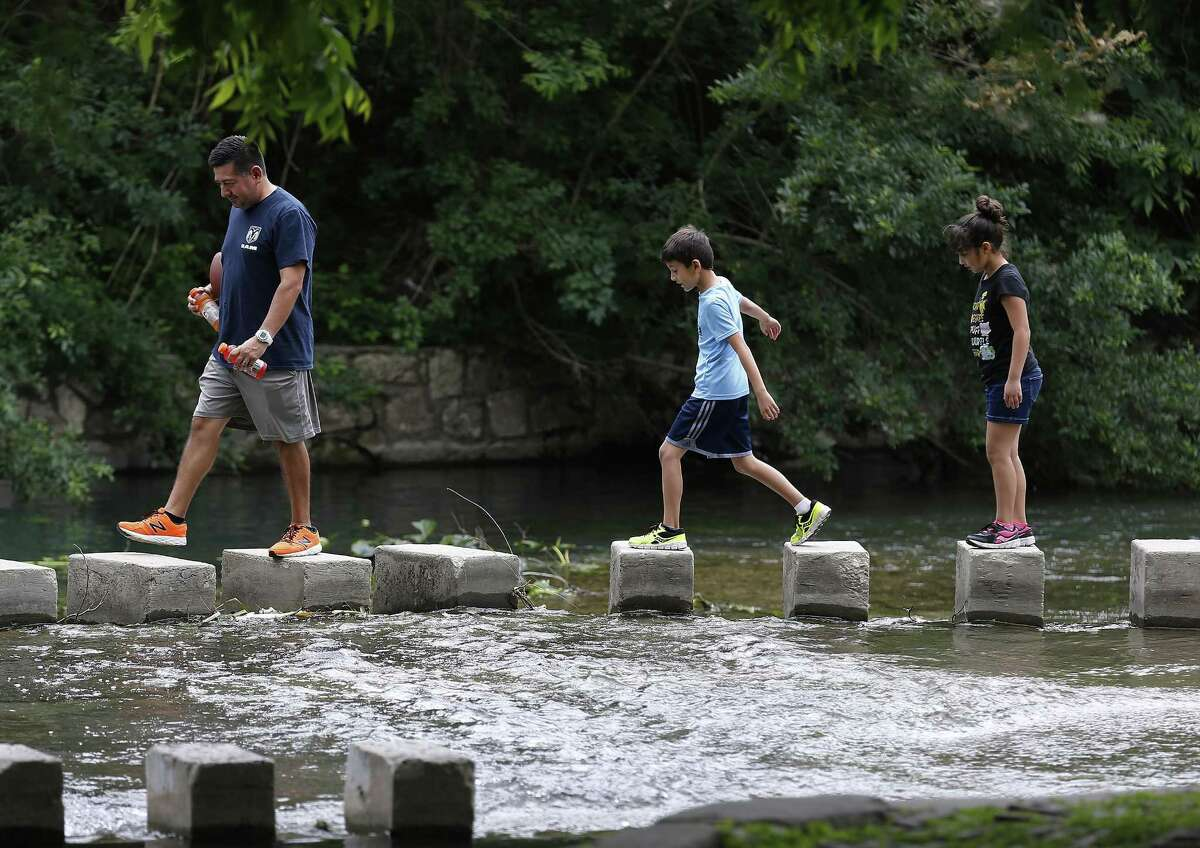 A family traverses the low-water crossing bridge as campers stake a spot at Brackenridge Park to celebrate Easter weekend with family and friends on April 15, 2017.