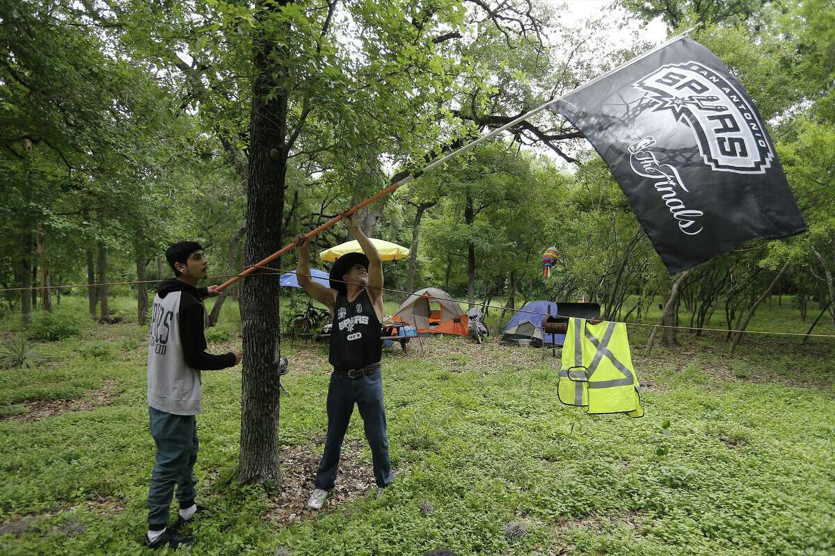 Daniel Garza (right) and Robert Vasquez look to find a good spot to hoist their Spurs flag while camping at Brackenridge Park on Saturday, Apr. 15, 2017. In annual fashion, campers staked a spot at Brackenridge to celebrate Easter weekend with family and friends. The city lifted the curfew on city parks on Thursday so people could claim their favorite camping spots. Seemingly quieter than usual some campers enjoyed the respite from city noise.