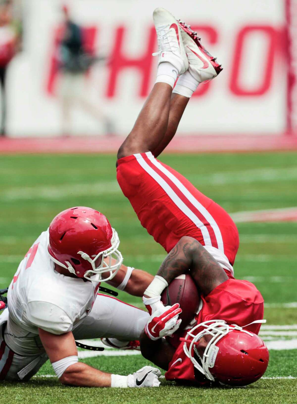 Houston safety Colln Wilder, left, brings down wide receiver Keith Corbin during the University of Houston Red-White Game at TDECU Stadium on Saturday, April 15, 2017, in Houston.