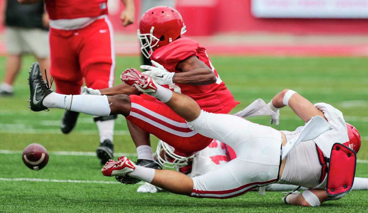 Houston wide receiver Derek McLemore, left, fumbles as he is hit by safety Collin Wilder during the University of Houston Red-White Game at TDECU Stadium on Saturday, April 15, 2017, in Houston.
