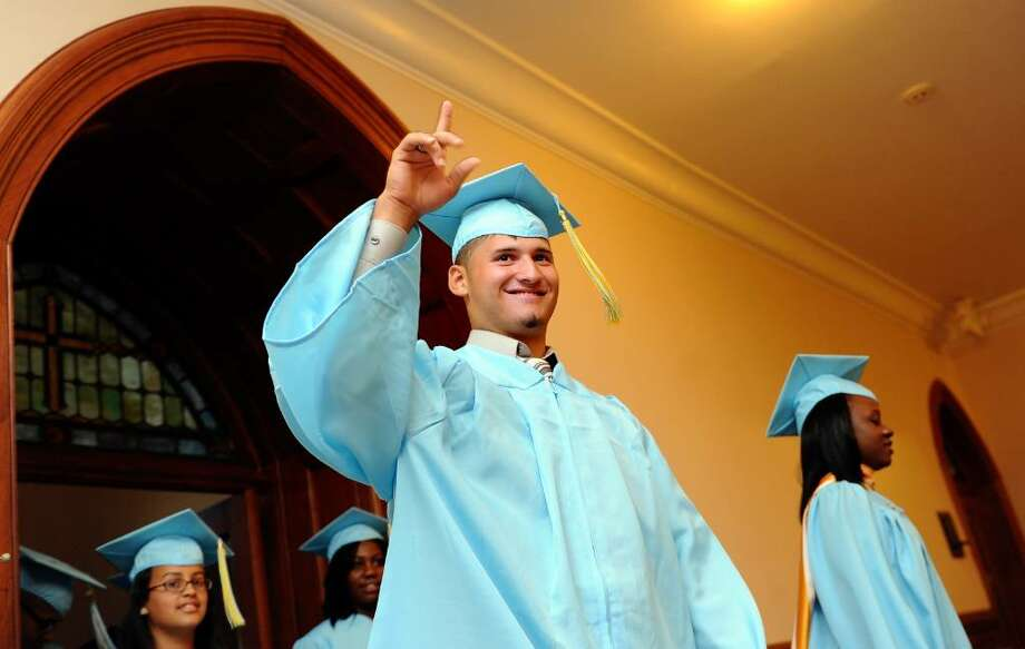 David Vega, of Bridgeport, waves to his family as he walks into St. Augustine Cathedral in Bridgeport with his fellow graduates for the 2010 Kolbe Cathedral High School graduation ceremony Thursday June 3. Photo: Autumn Driscoll / Connecticut Post