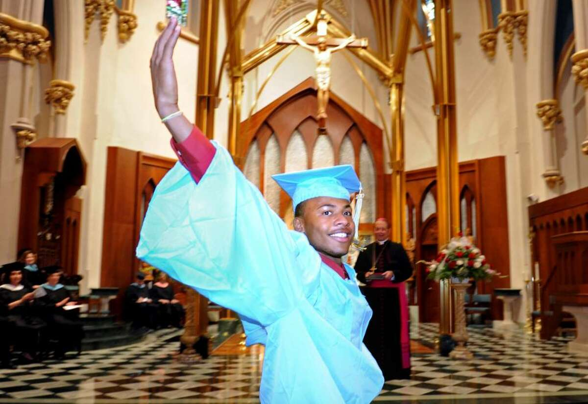 Ronnie Underwood throws his arms up as he goes forward to accept his diploma from Bishop William Lori during the 2010 Kolbe Cathedral High School graduation ceremony Thursday June 3 at St. Augustine Cathedral in Bridgeport.