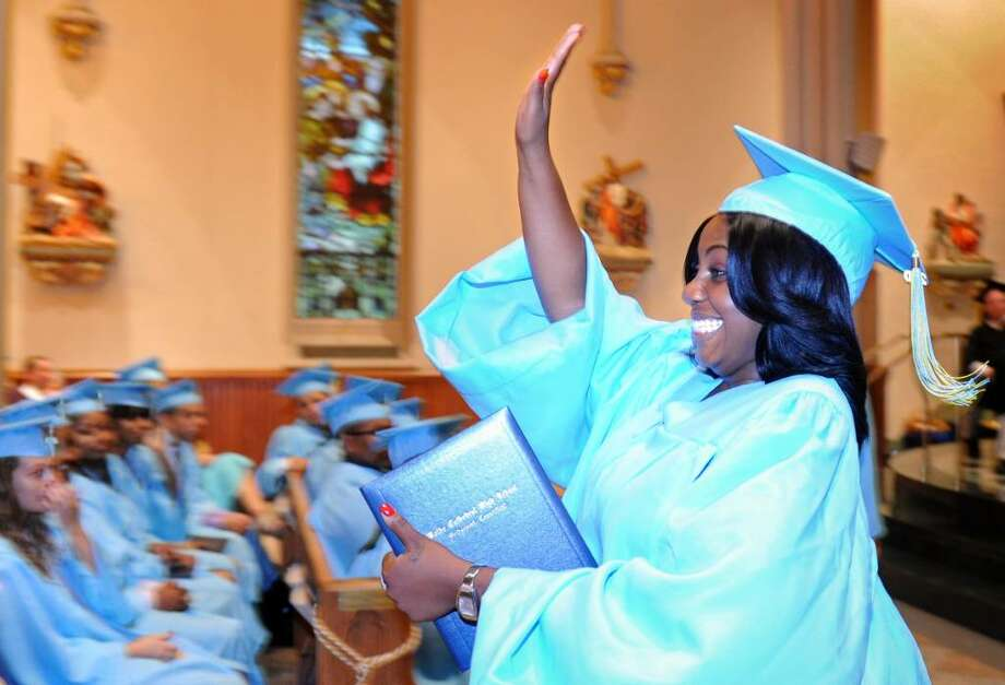 Shikara Watson, of Bridgeport, waves to her family as she walks back to her seat with diploma in hand during the 2010 Kolbe Cathedral High School graduation ceremony Thursday June 3 at St. Augustine Cathedral in Bridgeport. Photo: Autumn Driscoll / Connecticut Post