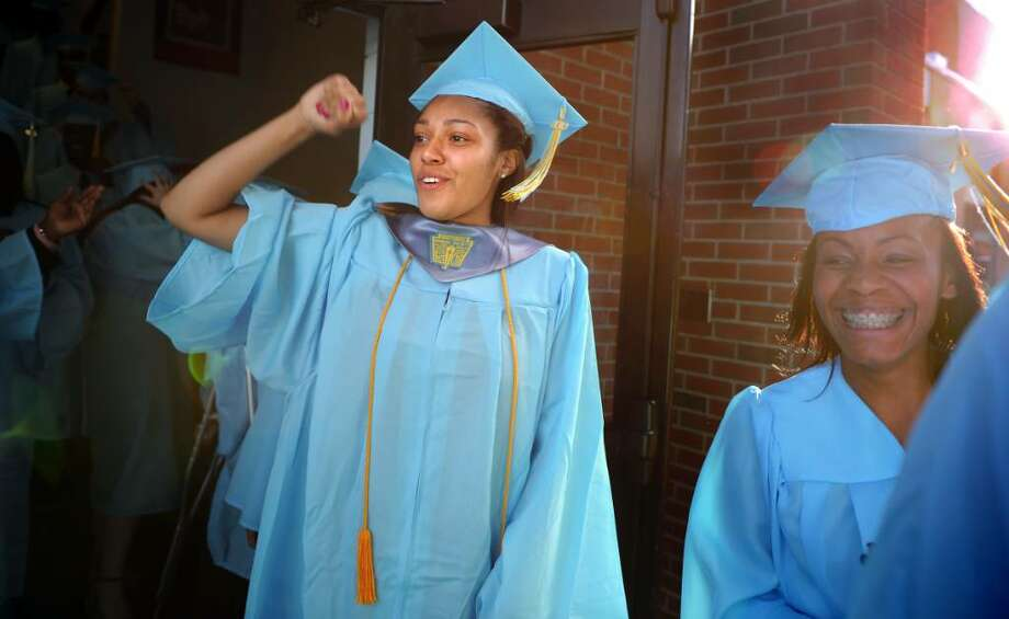 Malaysia Jimenez, of Seymour, pumps her fist  as she marches out of the gym with her fellow graduates for the 2010 Kolbe Cathedral High School graduation ceremony Thursday June 3 at St. Augustine Cathedral in Bridgeport. Photo: Autumn Driscoll / Connecticut Post