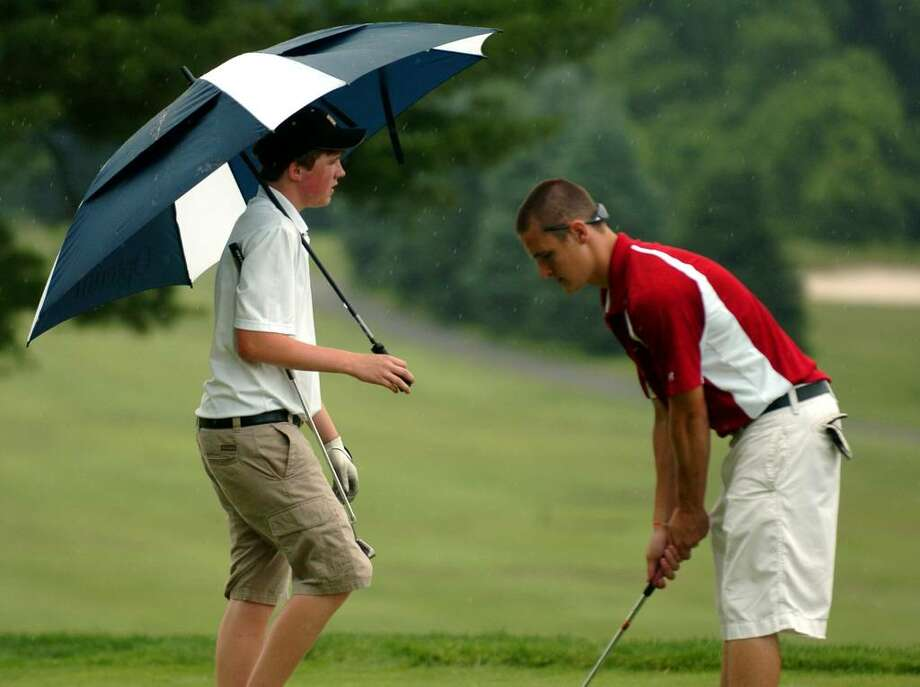 Trumbull's Chris Sarosky carries an umbrella as St. Joseph's Brian Kelly makes a practice stroke for his putt on the ninth hole, during boys FCIAC Championship golf action at Fairchild Wheeler Golf Course in Fairfield, Conn. on Thursday June 03, 2010. Just after this, a thunderstorm swept through the area causing the game to be suspended for about 45 minutes. Photo: Christian Abraham / Connecticut Post