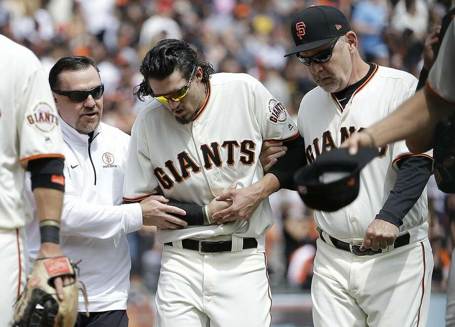 San Francisco Giants left fielder Jarrett Parker, center, walks off the field with trainer Dave Groeschner, left, and manager Bruce Bochy after catching a fly ball hit Colorado Rockies' DJ LeMahieu during the fourth inning of a baseball game in San Francisco, Saturday, April 15, 2017. Parker was injured on the play and left the game. (AP Photo/Jeff Chiu) Photo: Jeff Chiu, Associated Press