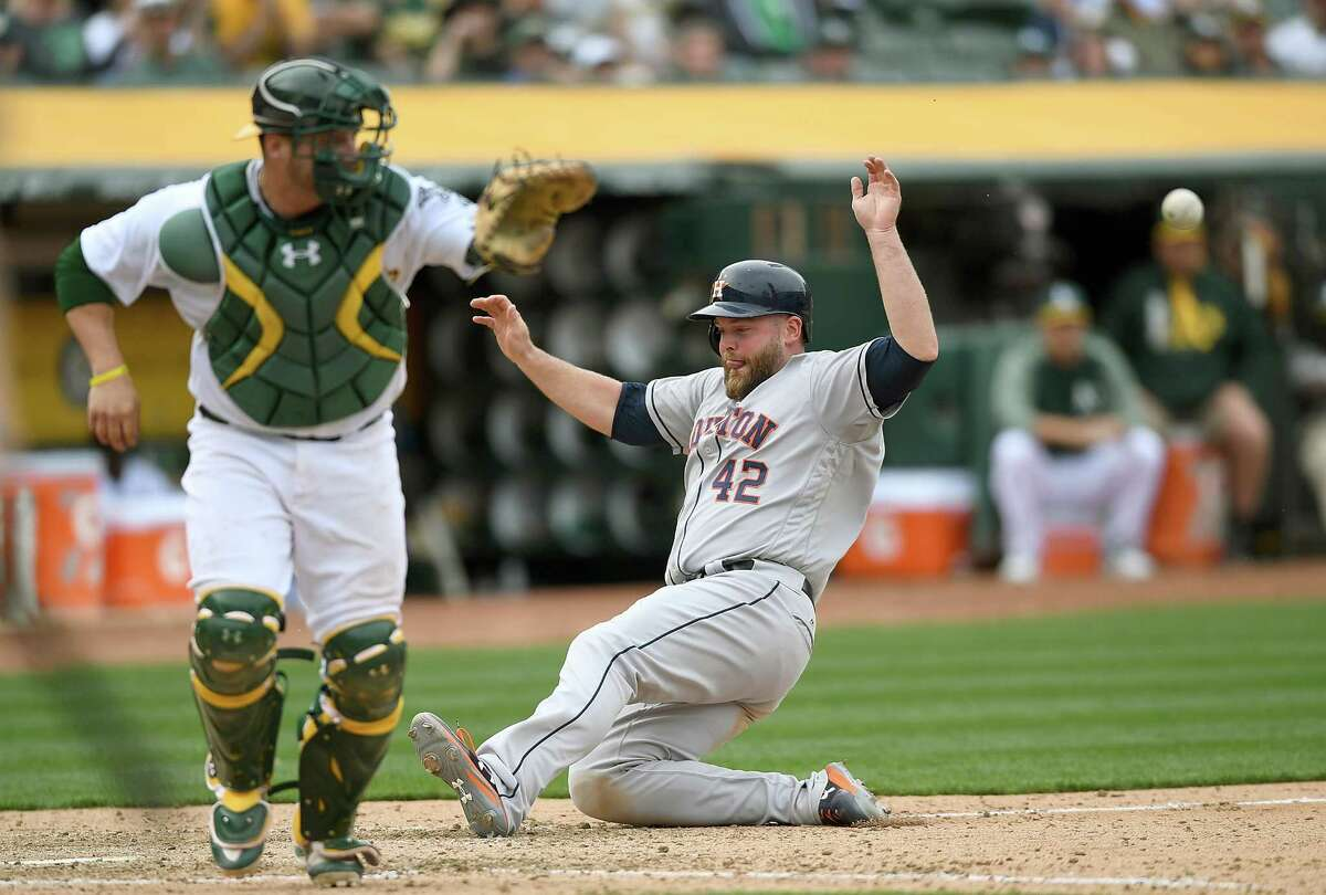 OAKLAND, CA - APRIL 15: Brian McCann #16 of the Houston Astros scores the go ahead run on a sacrifice fly from Norichika Aoki #3 against the Oakland Athletics in the top of the eighth inning at Oakland Alameda Coliseum on April 15, 2017 in Oakland, California. All players are wearing #42 in honor of Jackie Robinson Day.