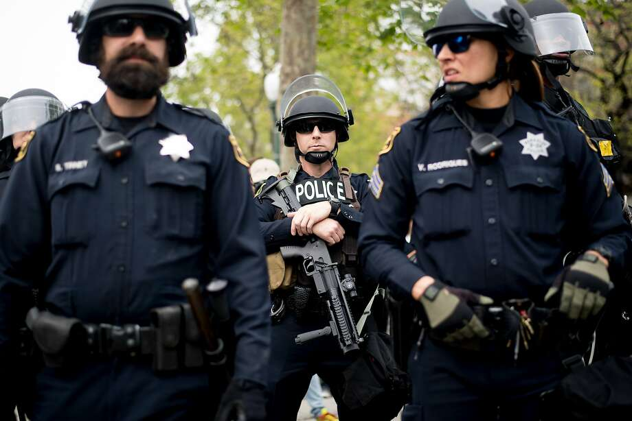 Police officers stand by as protesters face off April 15 in Berkeley. Officials changed the municipal code Friday to give the city manager the ability to issue rules at unauthorized events. Photo: Noah Berger, Special To The Chronicle