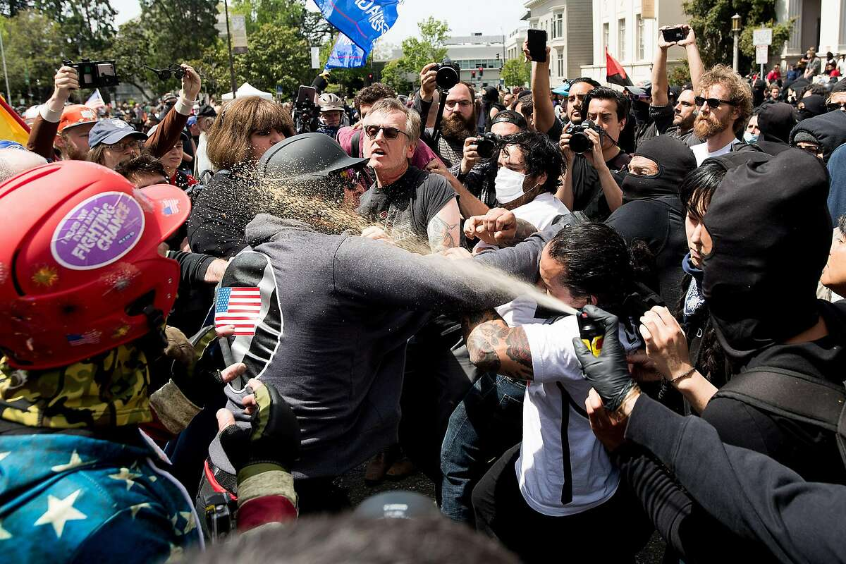 A protester against then-President Donald Trump sprays chemical irritant on a pro-Trump demonstrator on April 15, 2017. Charges of rioting stemming from this melee and two in Southern California were reinstated Thursday against members of the Rise Above Movement.