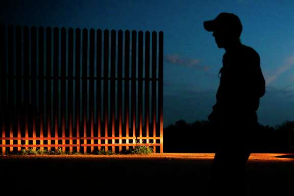 A Border Patrol agent guards a gap in the border fence in Penitas, west of McAllen. The Trump administration wants to expedite the hiring of 5,000 new agents.