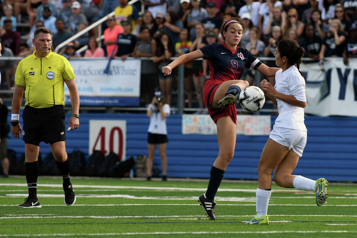 Katy Tompkins senior midfielder JoAnnie Ramos, left, worls the ball against a Pflugerville Hendrickson defender during the second period of their Class 6A Girls Final matchup at the 2017 UIL Soccer State Championships at Birkelbach Field in Georgetown on Saturday, April 15, 2017. (Photo by Jerry Baker/Freelance)
