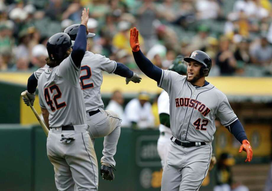 Houston Astros George Springer, right, celebrates after hitting a two-run home run off Oakland Athletics' Sean Doolittle in the eighth inning of a baseball game Saturday, April 15, 2017, in Oakland, Calif. (AP Photo/Ben Margot) Photo: Ben Margot, STF / Copyright 2017 The Associated Press. All rights reserved.