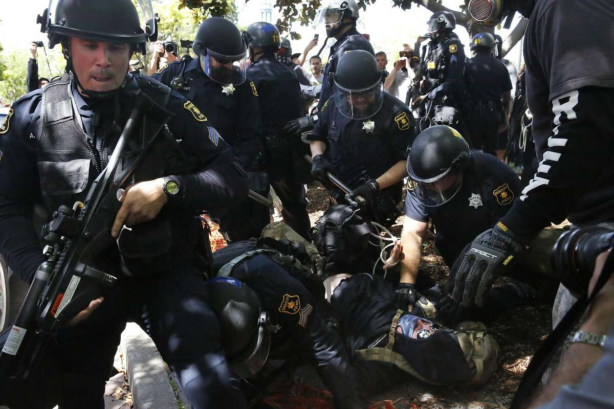 """Berkeley police officers detain someone during a rally called """"Patriot's Day Free Speech Rally"""" in Martin Luther King Jr. Civic Center Park April 15, 2017 in Berkeley. Charges of rioting stemming from this melee and two in Southern California were reinstated Thursday against members of the Rise Above Movement."""