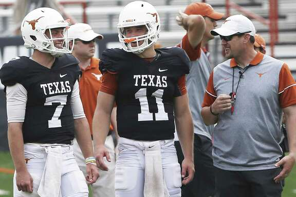 Quarterbacks Shane Buechele (7) and Sam Ehlinger (11) share a laugh with coach Tom Herman as the Texas Longhorns play their spring game on April 15, 2017, in Austin.