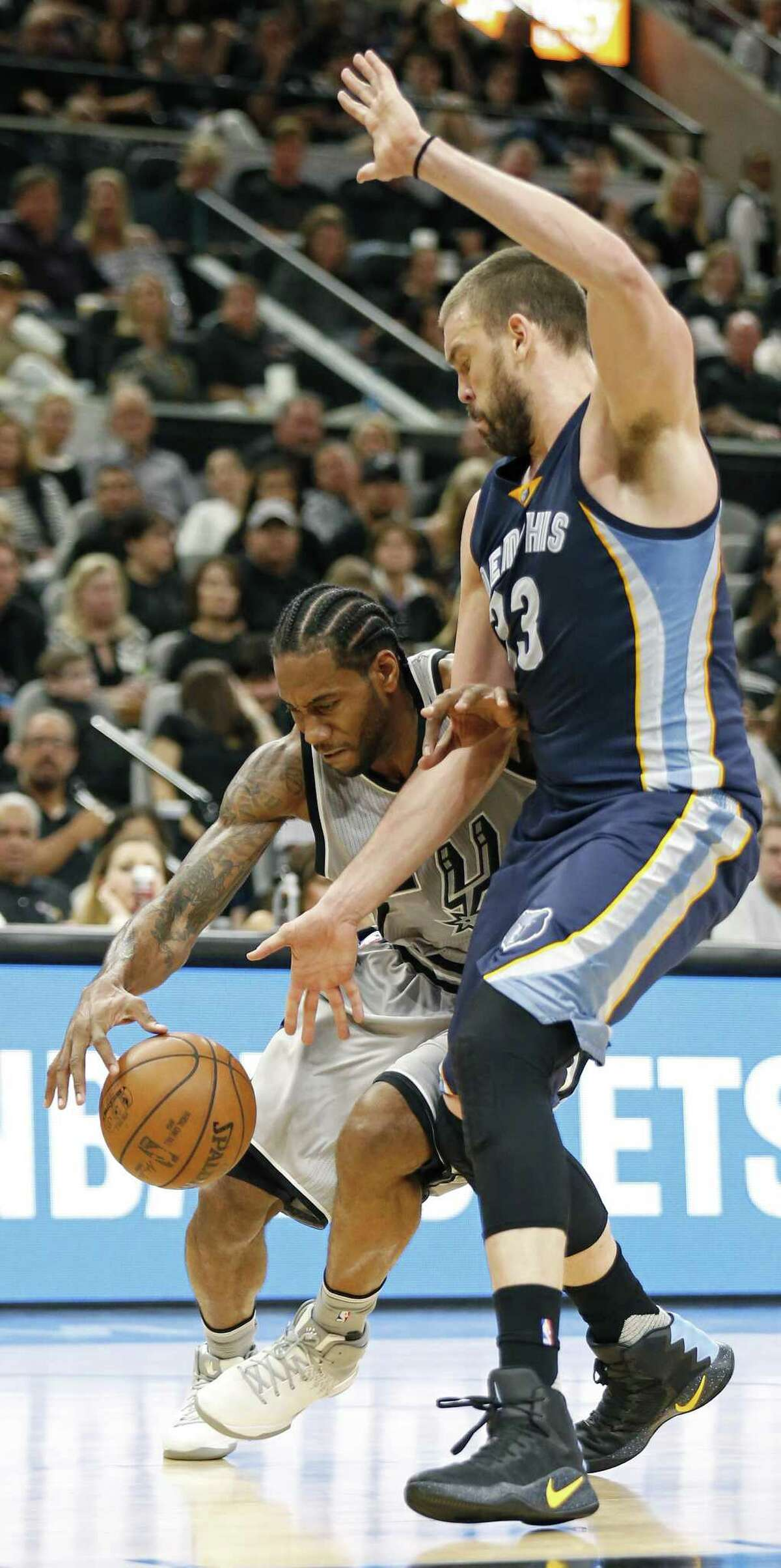 The Spurs' Kawhi Leonard tries to maneuver around Grizzlies center Marc Gasol during the first half. Leonard and Gasol finished with 32 points apiece to lead their respective teams.