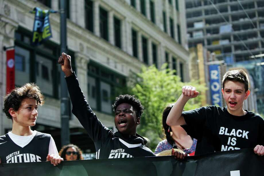 From left Owen Moriarty, 13, Bryce Green, 12, and Danilo Petrovic, 13, teammates on the Seattle Future basketball team, take part in a Black Lives Matter demonstration through the streets of downtown Seattle, Saturday, April 15, 2017. Photo: SEATTLEPI.COM / SEATTLEPI.COM