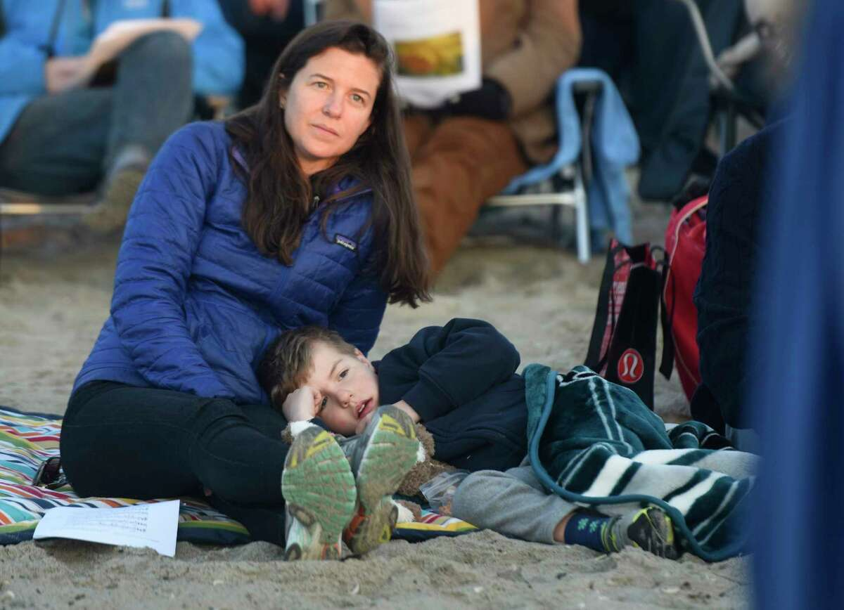 Riverside's Elizabeth DeHaven and her son, Henry DeHaven, 5, cozily watch First Congregational Church of Greenwich's Easter Sunrise Beach Service at Greenwich Point Park in Old Greenwich, Conn. Sunday, April 16, 2017. A large group gathered to take part in song and prayer, led by the Rev. Patrick Collins, as the sun rose above a cross on the beach.