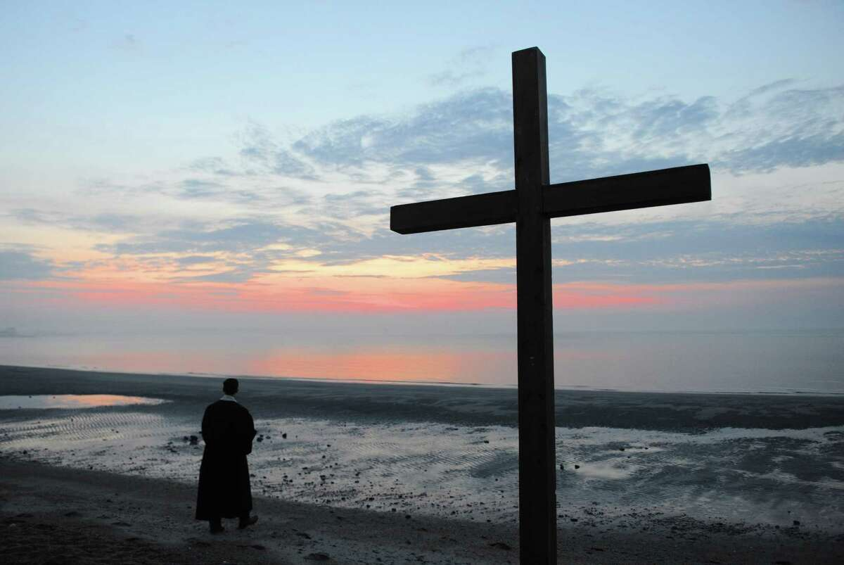 The Rev. Patrick Collins walks on the beach before leading First Congregational Church of Greenwich's Easter Sunrise Beach Service at Greenwich Point Park in Old Greenwich, Conn. Sunday, April 16, 2017. A large group gathered to take part in song and prayer, led by the Rev. Patrick Collins, as the sun rose above a cross on the beach.