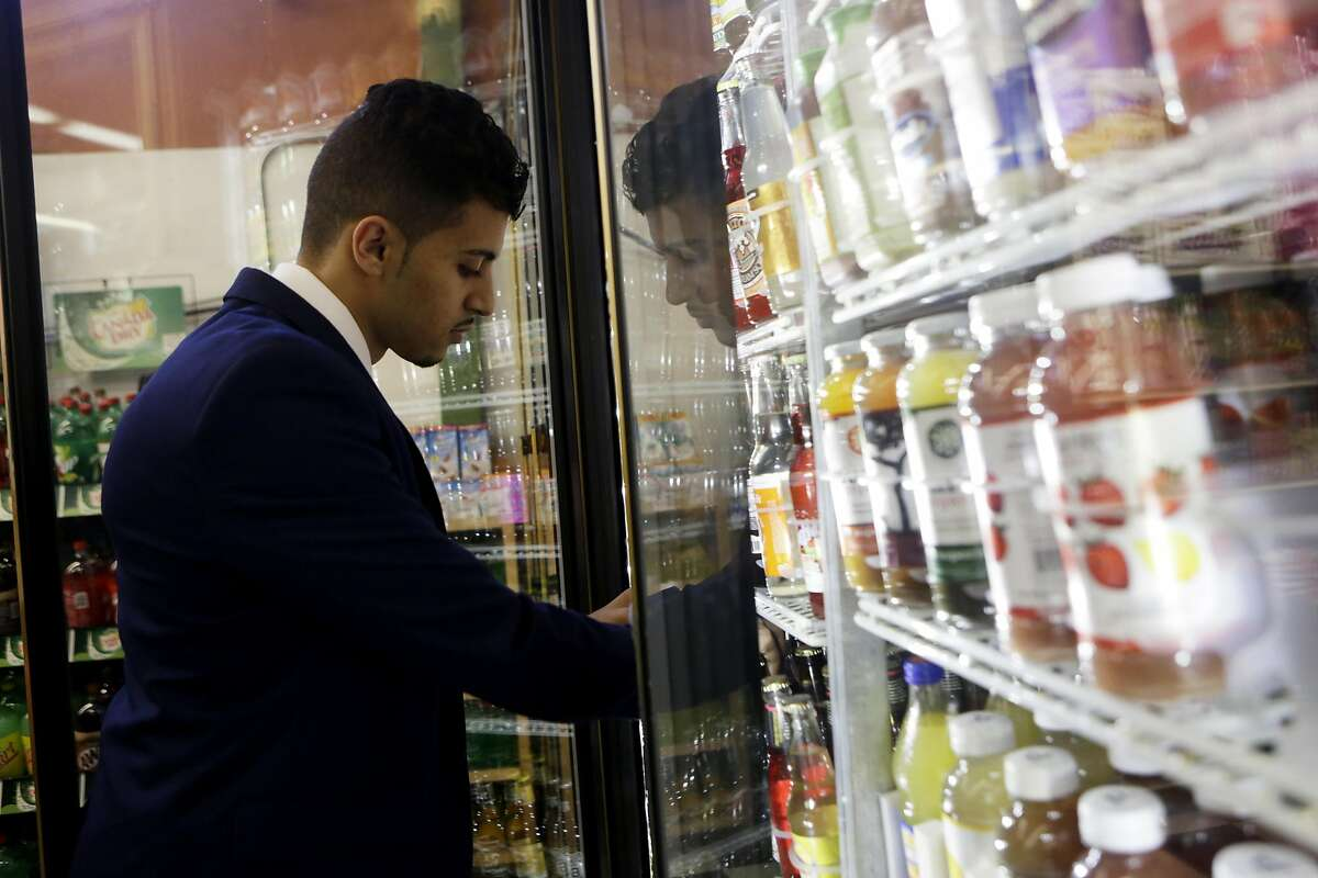 Murad Hussein, the owner of Ashby Supermarket, looks through sodas in the fridge to take inventory on Friday in Berkeley.