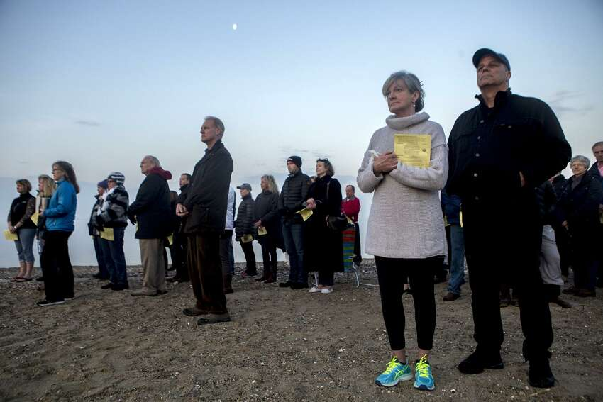 Sue and Tom Cello look toward the rising sun as the Benediction is read at the end of the Easter Sunrise Service at Bayley Beach on Sunday, April 16, 2017. The Rev. John Livingston from The United Church of Rowayton and the Rev. Karen Eiler from Rowayton United Methodist Church led the service.