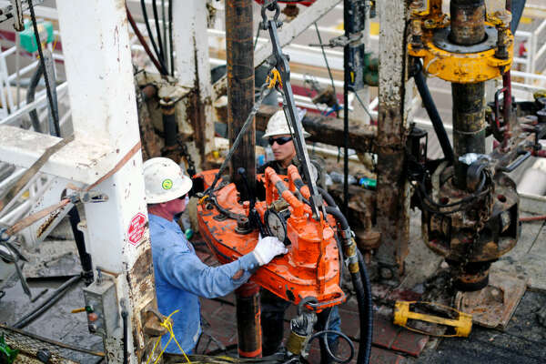 Kevin Giddings, left, and Noe Olvera, right, add a section of casing down a vertical well on the floor of Trinidad Rig 433 on Nov. 2, 2016, in Midland County.