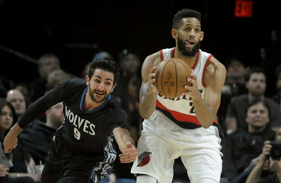 Minnesota Timberwolves guard Ricky Rubio reaches in to try and steal the ball from Portland Trail Blazers guard Allen Crabbe during the first half of an NBA basketball game in Portland, Ore., Thursday, April 6, 2017. (AP Photo/Steve Dykes) Photo: Steve Dykes, Associated Press