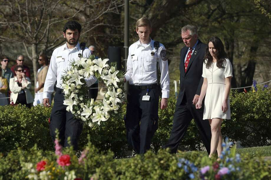 Members of the Virginia Tech Rescue Squad carry a wreath presented by Virginia Gov. Terry McAuliffe, second right, and his daughter Dori McAuliffe, right, on the Virginia Tech campus in Blacksburg, Va,. Sunday, April 16 2017, during a 10th anniversary observance of the mass shooting that killed 32. (Matt Gentry/The Roanoke Times via AP) Photo: Matt Gentry, Associated Press
