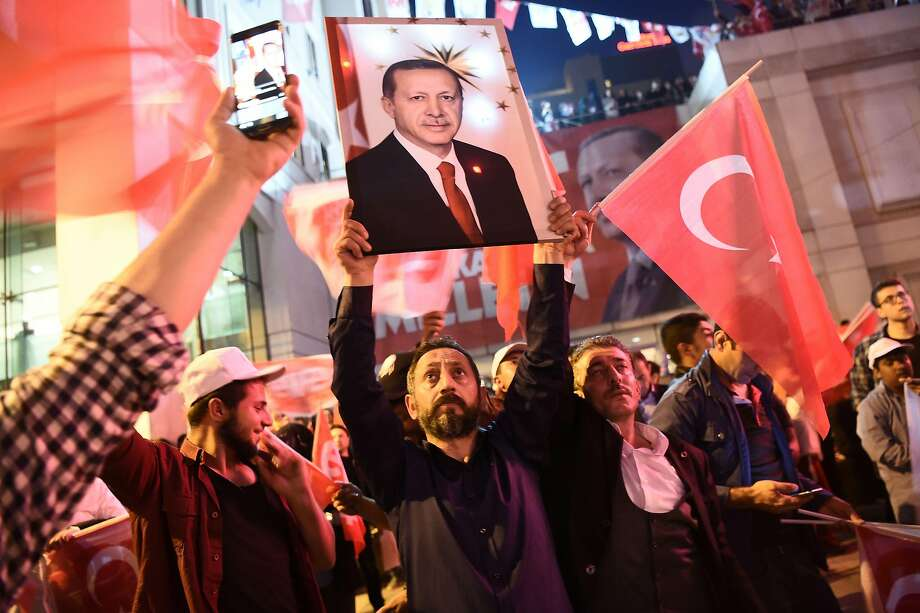 Supporters of the referendum giving Turkish President Recep Tayyip Erdogan expanded authority raise his picture in celebration during a rally in Istanbul. Photo: OZAN KOSE, AFP/Getty Images
