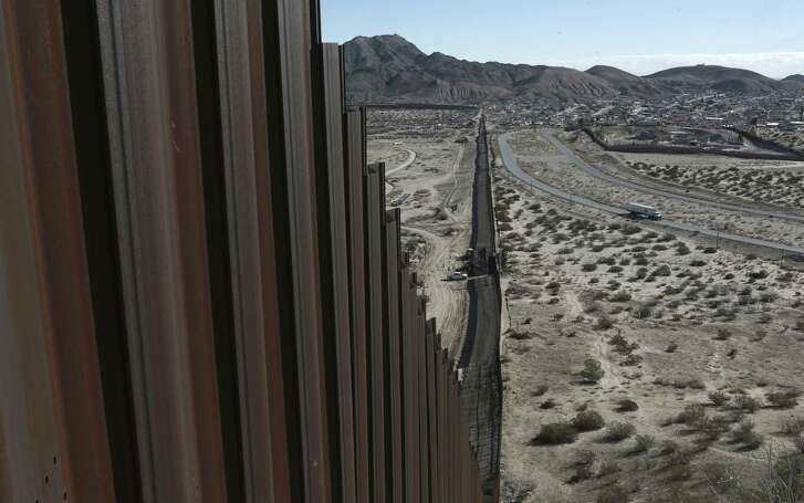 """FILE - This Jan. 25, 2017, file photo shows a truck driving near the Mexico-US border fence, on the Mexican side, separating the towns of Anapra, Mexico and Sunland Park, New Mexico. President Donald Trump will face many obstacles in building his """"big, beautiful wall"""" on the U.S.-Mexico border, including how to pay for it and how to contend with unfavorable geography and the legal battles ahead.  (AP Photo/Christian Torres, File)"""