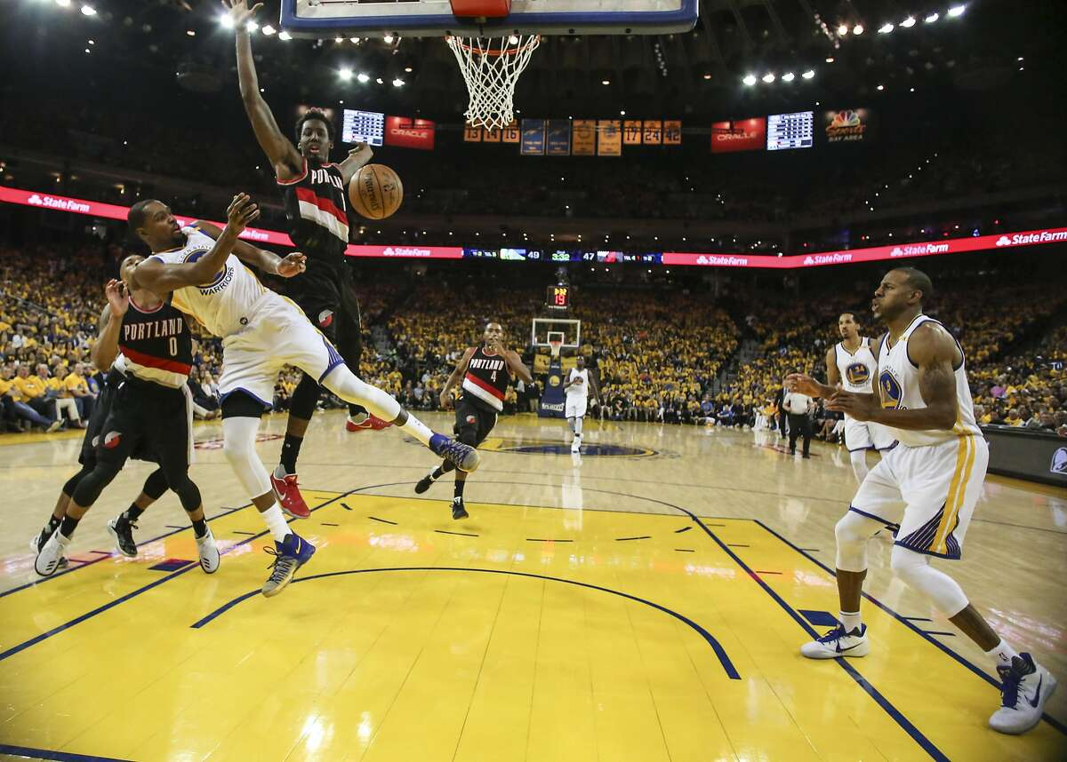 Golden State Warriors' Kevin Durant passes off to Andre Iguodala under the basket during Game 1 of the First Round of the Western Conference 2017 NBA Playoffs at Oracle Arena on Sunday, April 16, 2017 in Oakland, Calif.