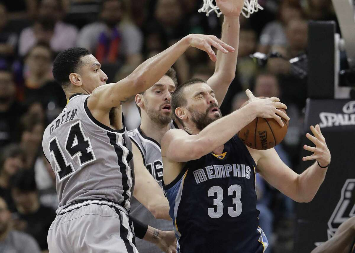 Memphis Grizzlies center Marc Gasol (33) is defended by San Antonio Spurs guard Danny Green (14) and center Pau Gasol during the second half in Game 1 of a first-round NBA basketball playoff series, Saturday, April 15, 2017, in San Antonio. San Antonio won 111-82. (AP Photo/Eric Gay)