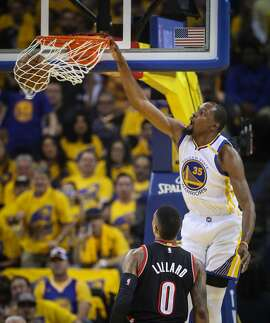 Golden State Warriors' Kevin Durant dunks as Portland Trailblazers' Damian Lillard watches in the first quarter during Game 1 of the First Round of the Western Conference 2017 NBA Playoffs at Oracle Arena on Sunday, April 16, 2017 in Oakland, Calif.