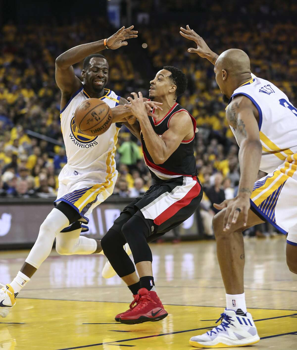 Portland Trailblazers' CJ McCollum loses the ball guarded by Golden State Warriors' Draymond Green and David West in the second quarter during Game 1 of the First Round of the Western Conference 2017 NBA Playoffs at Oracle Arena on Sunday, April 16, 2017 in Oakland, Calif.